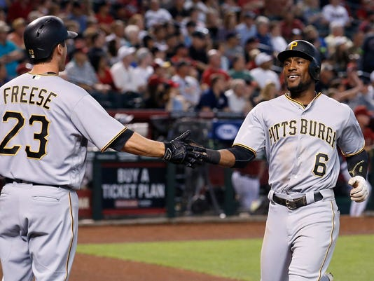 Pittsburgh Pirates' Starling Marte (6) slaps hands with David Freese (23) after scoring a run against the Arizona Diamondbacks during the third inning of a baseball game Sunday, April 24, 2016, in Phoenix. (AP Photo/Ross D. Franklin)
