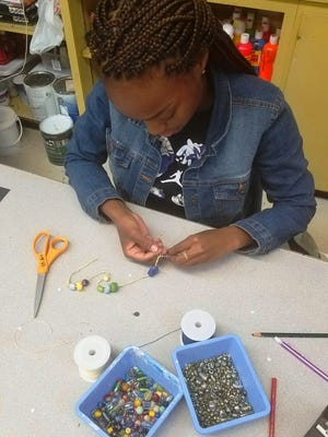A Maclay student strings beads for an empathy bracelet.