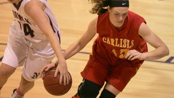 Norwalk junior Kierstin Vaske pulls the ball away from Carlisle senior Mary Grace Wachal. Carlisle won 57-36 in Norwalk Tuesday night.