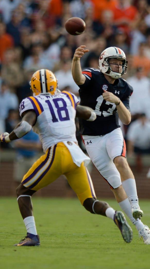 Auburn quarterback Sean White (13) throws a pass as