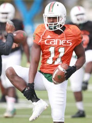 Miami receiver Rashawn Scott goes through stretching drills Tuesday.