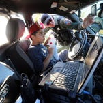 Rutherford County Sheriff's Deputy Matt Kunce Tuesday shows Justin Carvajal, 10, what's inside his patrol car at the Smyrna Night Out at Lee Victory Park.
