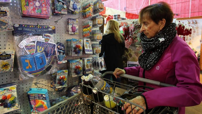 Ellen Berkowitz of Riverdale in the Bronx, shops for Hanukkah gifts at Stew Leonard's in Yonkers, Nov. 27, 2016. She's heading to Florida in a couple of weeks and plans to pack her holiday treats in the car, which they'll ship to Florida.