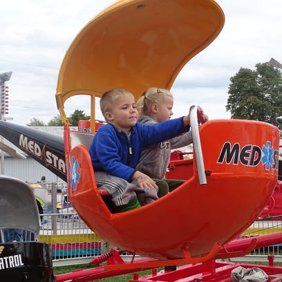 Children take to the air on the midway Friday at the