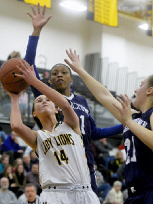 Red Lion's Kynslee Shepherd takes a shot against Dallastown's Amari Johnson, back, and Sabrina Stough in the first half of Friday's girls' game at Red Lion High School. The Lions topped the Wildcats, 45-40. (Chris Dunn -- Daily Record/Sunday News)