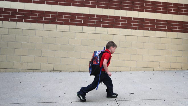 A student at Indianapolis Public Schools' School 44 heads back to school on the first day of classes on Aug. 3, 2015.