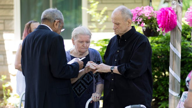 Thelma Thompson slips John's wedding ring onto his finger during their wedding ceremony in the front yard of their home in Shively.