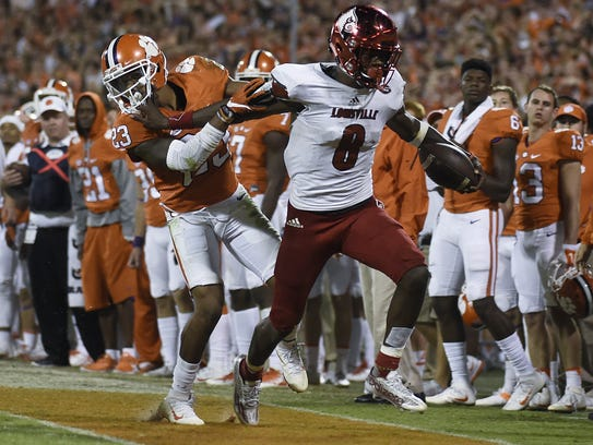 Louisville quarterback Lamar Jackson fights of the