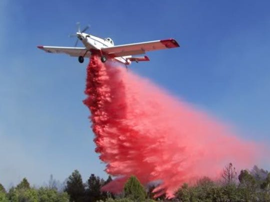 A single engine air tanker drops slurry during a fire.