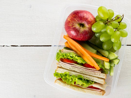 Lunchbox with sandwich, vegetables, fruit on white