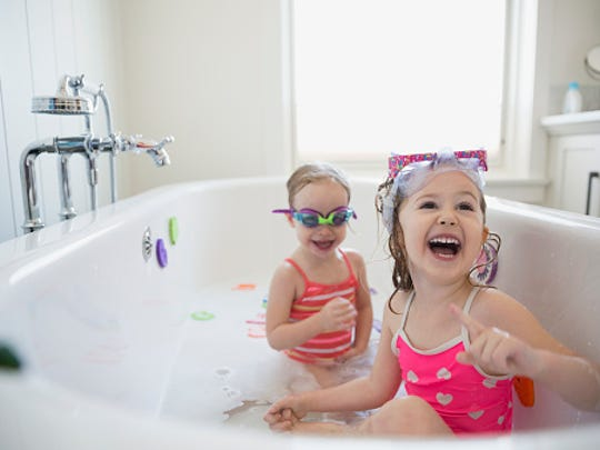 Laughing sisters playing in bubble bath