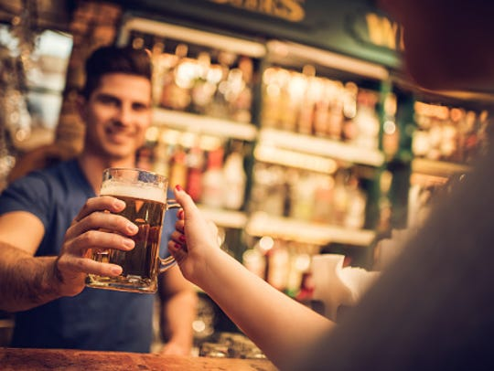 Close-up of bartender giving beer to a customer in