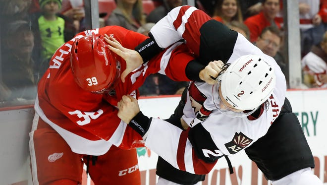 Red Wings right wing Anthony Mantha (39) fights Coyotes defenseman Luke Schenn (2) in the second period, Tuesday, Dec. 13, 2016, in Detroit.
