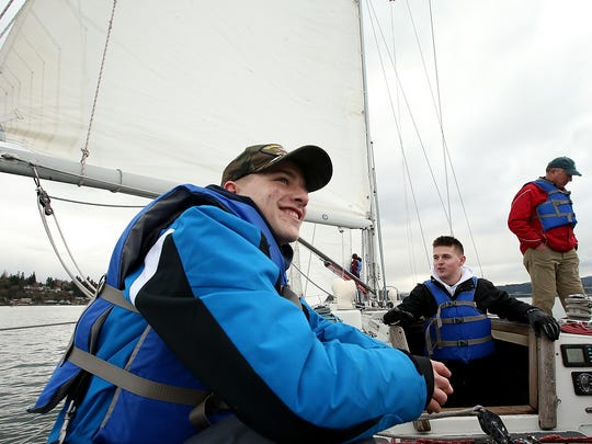 South Kitsap NJROTC students Logan Destrada, 16, (left) and Joshua Ray, 17, (center) relax for a moment as the Lively sails through Sinclair Inlet on Friday, March 2, 2018.