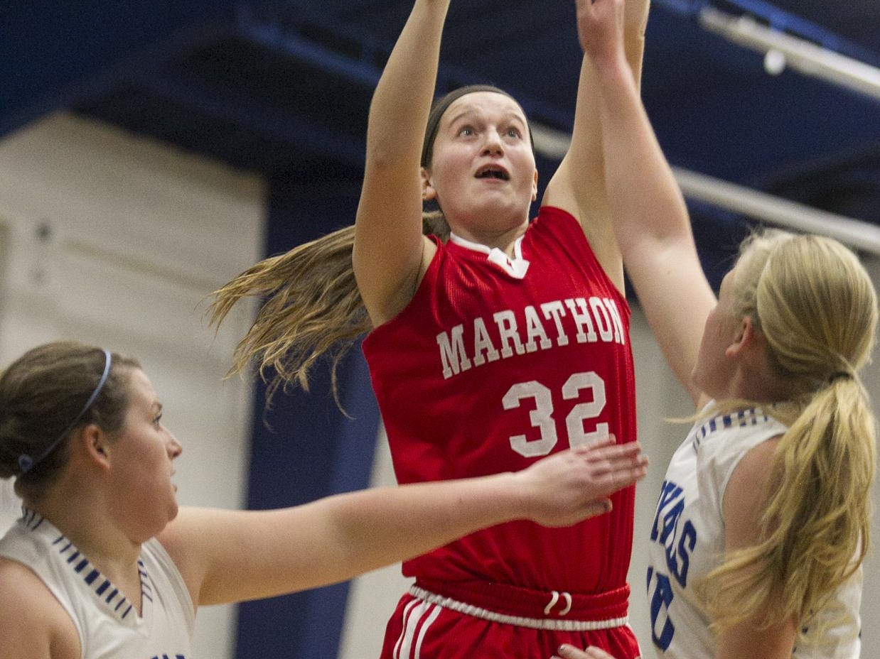 Marathon's Natasha Hanke, center, shoots over Assumption's Joelynn Frisch, left, and Macyn Krings, right, during the first half of the Marawood Conference girls basketball game at Assumption High School in Wisconsin Rapids, Tuesday, Dec. 1, 2015.