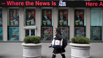 A woman walks past the News Corp. headquarters building displaying posters featuring Fox News Channel personalities including  Bill O'Reilly, top center, in New York, Wednesday, April 19, 2017. T