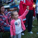 Emma Huber, 5, of Newark, plays with a sparkler Sunday evening before the fireworks display at OSU-Newark.