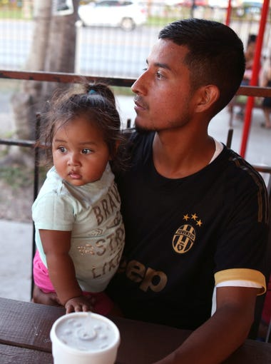 Ezequiel Rojas holds his daughter, Nayeli Rojas, 1 1/2, while watching his other daughter play at House of Burgers on October 8, 2017. Rojas sold his 1988 Buick LeSabre for $1,000 in order to gain the funds to apply for DACA. His DACA expired in April and he applied for residency through his wife in March.