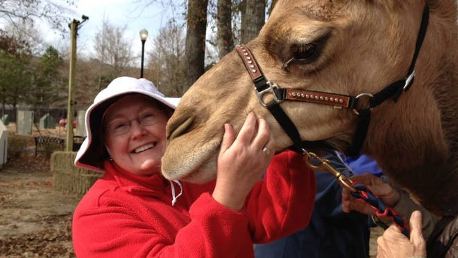 Parents & Kids publisher/editor Gretchen Cook cozies up to Frank the Camel at a previous Christmas Fest.