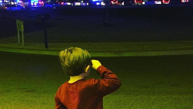 Charlie Martinez, 4, salutes the motorcade carrying the body of fallen MBN Agent Lee Tartt back home to Grenada.