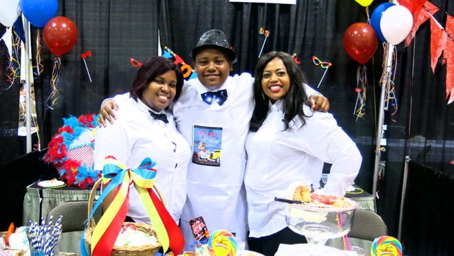 Gabrielle Ford (left) and Caddo Commissioner Stormy Gage-Watts flank Karrington watts at the Helen's Honey Bun Cakes Booth at Gentleman's Cooking Classic.