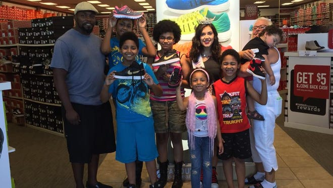 "Children who benefited from the ""Love through Laces"" project join Miss Cumberland County Olivia Cruz at Famous Footwear."