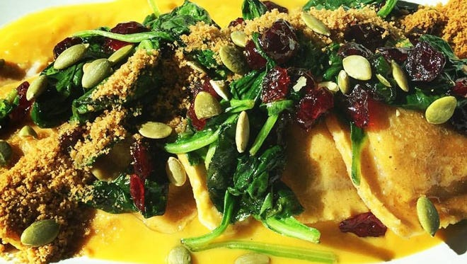 The Pumpkin Ravioli at Harvest Seasonal Grill & Wine Bar includes butternut squash purée, sage brown butter, cranberries, sautéed baby spinach, toasted pumpkin seeds and gingerbread dust.