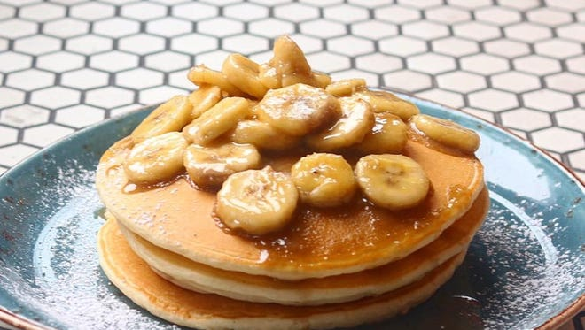 Pancakes topped with bananas and syrup at Cross and Orange.