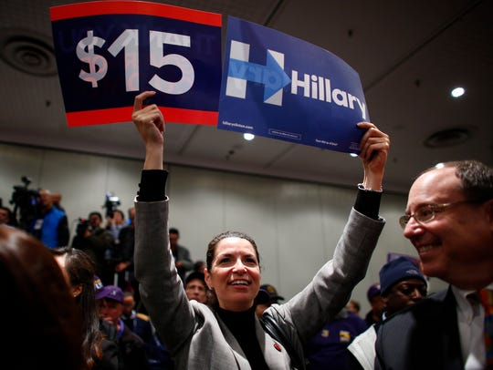A woman holds banners as Hillary Clinton speaks during