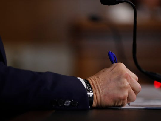 Former Texas Governor Rick Perry, President Donald Trump's choice for secretary of energy, takes notes during his confirmation hearing before the Senate Committee on Energy and Natural Resources on Thursday, Jan. 19, 2017, on Capitol Hill in Washington, D.C. The bracelet on his wrist is engraved with the name of Marine Pfc. Colton W. Rusk, an Orange Grove High School graduate who was killed Dec. 10, 2010, while serving in Afghanistan.