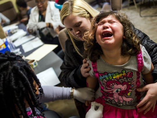 Flint resident Sarah Truesdail holds her daughter Gabriella Venegas, 5, as she screams out with tears rolling down her face while a health official pricks her finger with a needle for a free lead test in February 2016.