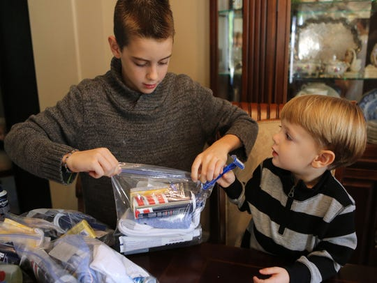 Isaac Wagner, 3, right, tries to add a razor to a kit