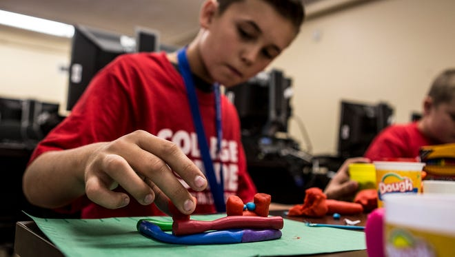 Caleb Gaynier builds a replica of his business out of play-dough during his week ling course, College Aspire at COTC in Coshocton.