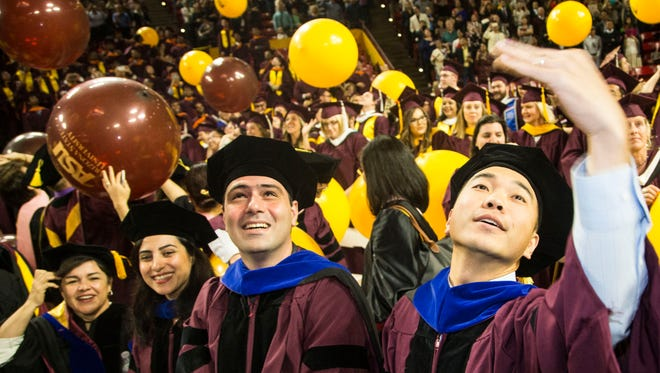 Wenzhe Xue (right), a biomedical graduate, celebrates after the commencement ceremony at ASU's Wells Fargo Arena on Dec. 12,  2016.