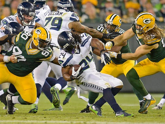 Green Bay Packers nose tackle B.J. Raji (90) and inside linebacker Clay Matthews (52) converge on running back Marshawn Lynch against the Seattle Seahawks at Lambeau Field.