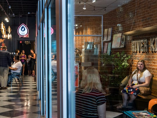 People grab drinks and food from the cafe as others spend time playing with cats in the cat room (right) during a soft opening of River Kitty Cat Cafe located along Main Street, in downtown Evansville, Ind., on Thursday, July 13, 2017.