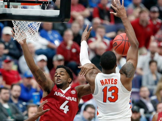 Arkansas' Daryl Macon (4) gets tangled up with Florida's Kevarrius Hayes (13) during the second half of an NCAA college basketball game in the quarterfinals of the Southeastern Conference tournament, Friday, March 9, 2018, in St. Louis. Arkansas won 80-72. (AP Photo/Jeff Roberson)