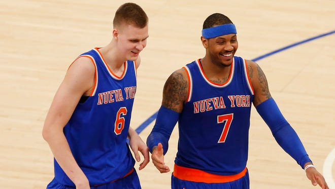 Mar 24, 2016; New York, NY, USA;  New York Knicks forward Kristaps Porzingis (6) and forward Carmelo Anthony (7) laugh on the court during second half time out against the Chicago Bulls at Madison Square Garden. The Knicks won 106-94. Mandatory Credit: Noah K. Murray-USA TODAY Sports