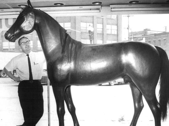 Robert S. Lull, owner of Weider's Hardware store, located at 257 Broad St. at the time, pats a plaster-of -paris horse, which has been in window since the store opened in 1938.