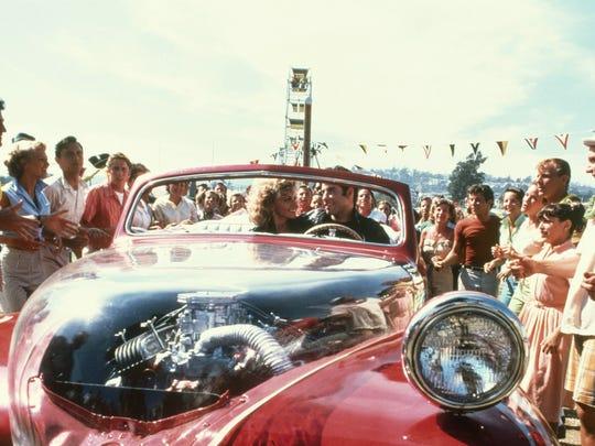 "Sandy (Olivia Newton-John) and Danny (John Travolta) take off at the end of ""Grease."""