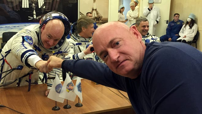 Astronaut Scott Kelly, left, fist bumps his twin brother, former astronaut Mark Kelly, through a glass partition before he launches on an almost yearlong trip on the International Space Station.