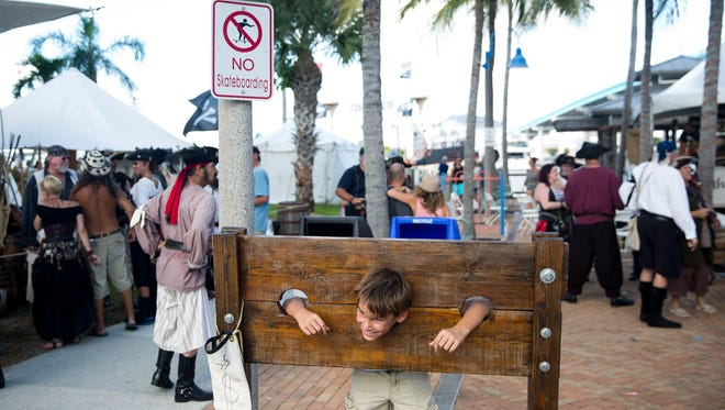 Braylon Hiller, 10, of Cape Coral, smiles as he is locked in a mock set of stocks during the last day of the 11th Annual Fort Myers Beach Pirate Festival on Sunday, Oct. 9, 2016.