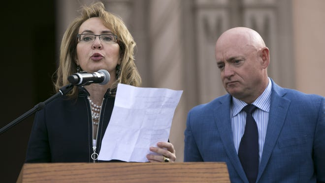 Former  U.S. Rep. Gabrielle Giffords speaks, as her husband, Mark Kelly looks on, during the memorial dedication for Tucson's January 8th Memorial at El Presidio Park in Tucson on Jan. 8, 2018. The dedication was held on the seven-year anniversary of the Tucson-area mass shooting that left six people dead and 13 others injured, including Giffords. The memorial is expected to be completed within the next two years.