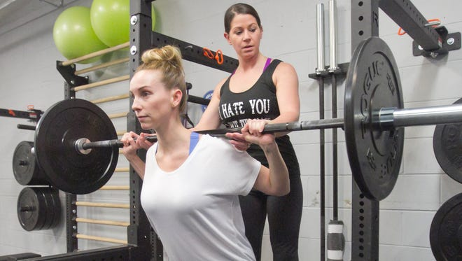 The Training Room owner/personal trainer Kim Keil, left, spots and coaches client Sylvia Porta, who lifts weights at the Brighton Township facility that opened earlier this year.