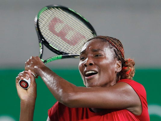 Venus Williams of the United States returns a ball to Belgium's Kirsten Flipkens in the women's tennis competition at the 2016 Summer Olympics in Rio de Janeiro, Brazil, Saturday, Aug. 6, 2016. (AP Photo/Vadim Ghirda)