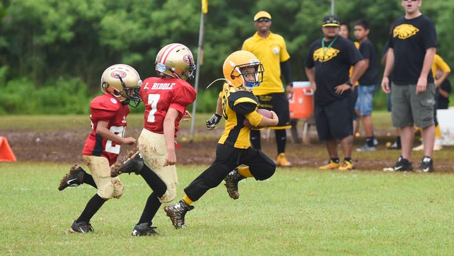 Island Eagles player Eric Tedtaotao (39) attempts to run the ball against the PXC Southside 49ers during their GNYFF Youth Football League game at University of Guam field in Mangilao on Sept. 13.
