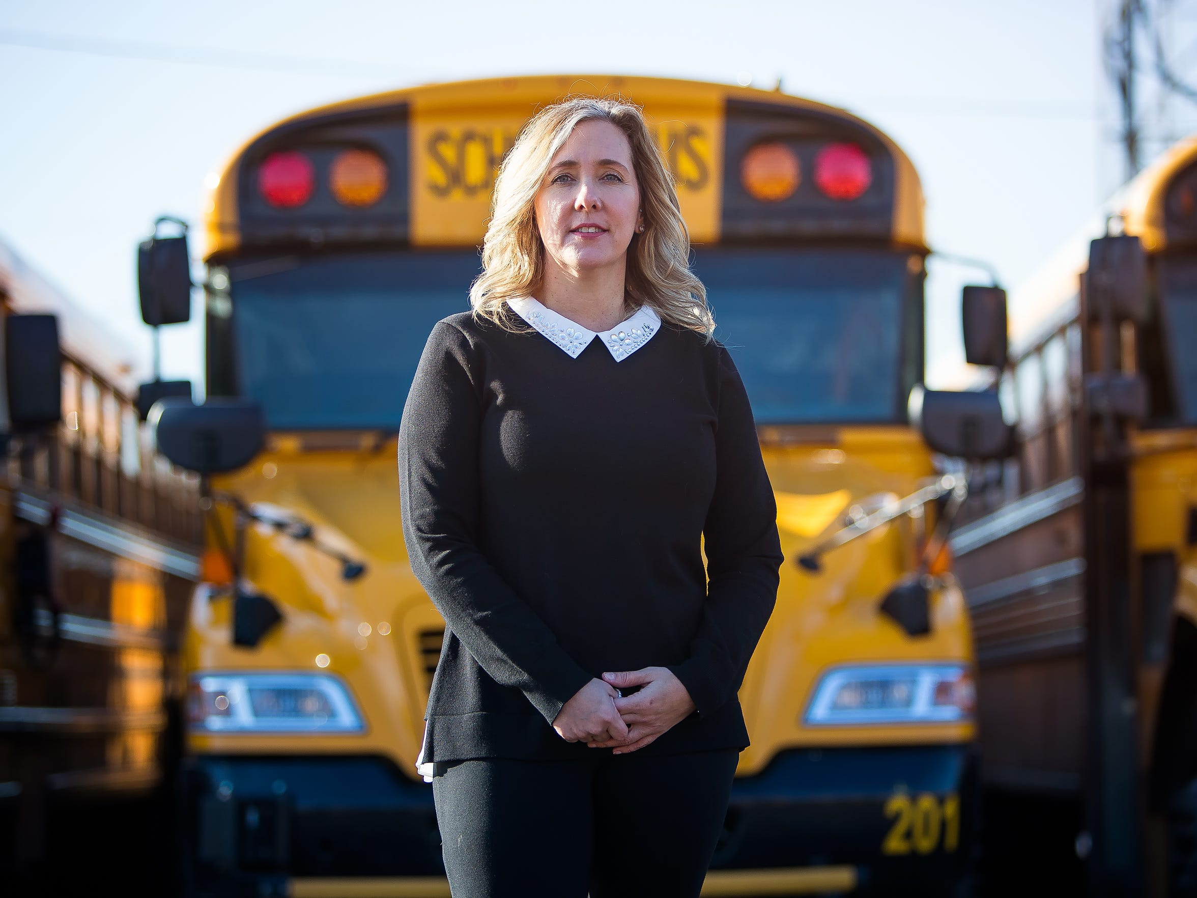 Transportation director Kelly Shahan, stands in front a line of school buses at the Red Clay Transportation Yard.