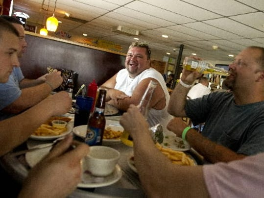 Shawn Davenport, center, of Manchester Township, and Rodd Huyett of Strinestrown, right, eat lunch with co-workers at 4-B s Tavern.