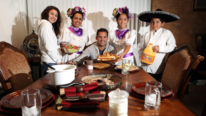 The Garcia Reyes Family: Palm Desert residents (from right) Carlitos Garcia, 11, Keanna Garcia, 13, Carlos Garcia, Marisol Reyes, 38, and their Italian exchange student Anita Cupidi, 16, before they sit down to their dinner at home on Friday, November 22, 2013 in Palm Desert, Calif.