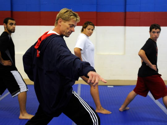 Tokey Hill teaches local students a martial arts move